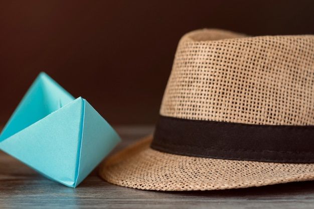 Concept of tourism, travel. blue paper boat and summer hat on the table.