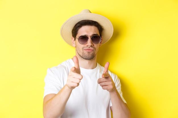 Concetto di turismo e vacanze. close-up di cool guy in estate cappello e occhiali da sole puntare il dito pistole alla fotocamera, in piedi su sfondo giallo.