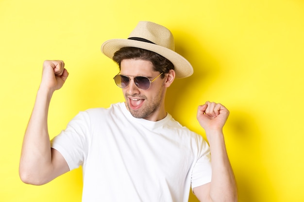 Concept of tourism and vacation. close-up of man enjoying holidays on trip, dancing and pointing fingers sideways, wearing sunglasses with straw hat, yellow background.