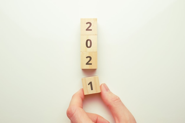 The concept of the transition to the new year 2021. hand holds a wooden block.