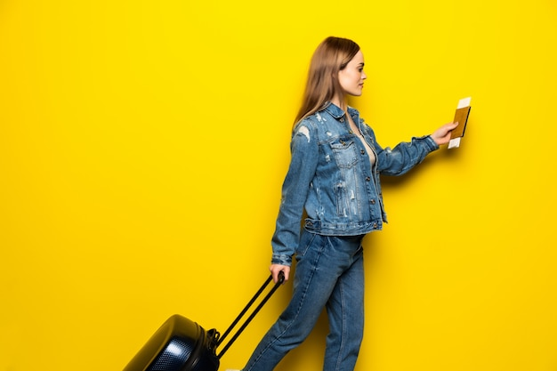 Concept of travel. happy woman girl with suitcase and passport run on yellow colored wall