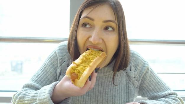 不健康な食品の概念。女性はファーストフードカフェでホットドッグを食べます。