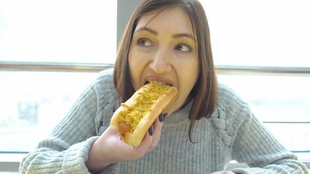 Concept unhealthy food. woman eats a hot dog at a fast food cafe.