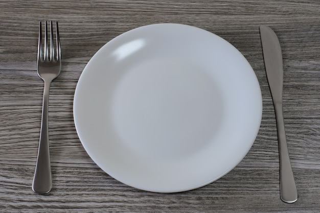 Concept of unhealthy nutrition and starvation. top view close up photo of empty clean plate and cutlery on wooden table