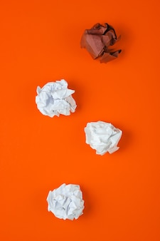 The concept of uniqueness, racial discrimination. white and brown crumpled paper balls on orange background. top view, minimalism business