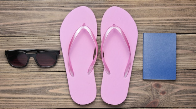 Concept of vacation on the beach, tourism. summer traveler background. flip flops, passport, sunglasses on wooden background.