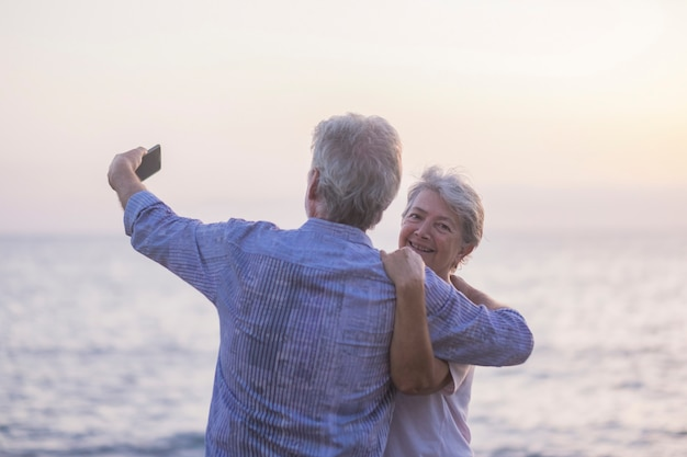 Concept of vacation, technology, tourism, travel and people - happy senior couple with cell phone phone on pebble beach laughing and joking hugging and making photo.