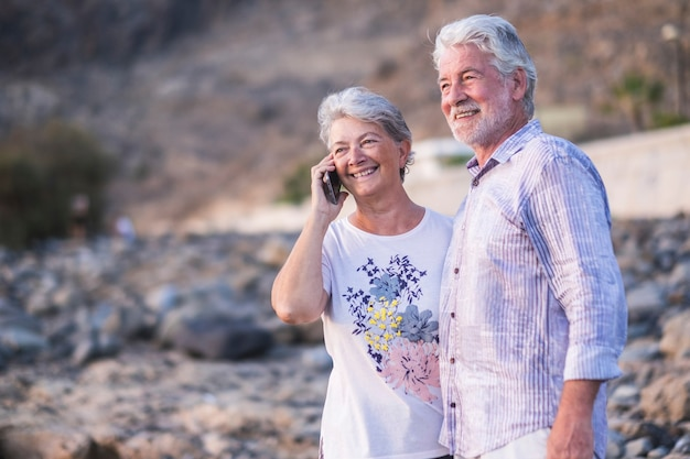 Concept of vacation, technology, tourism, travel and people - happy senior couple with cellular phone on mobile phone pebbles laughing and joking hugging and phoning.