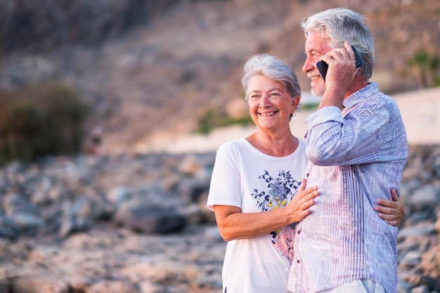 Concept of vacation, technology, tourism, travel and people - happy senior couple with cellular phone on phone on pebble beach laughing and joking. white hair
