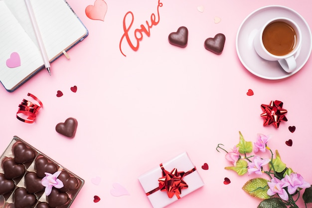 Concept valentine's day. chocolate candies and coffee, hearts on a pink background. flat lay copy space. greeting card and gift.