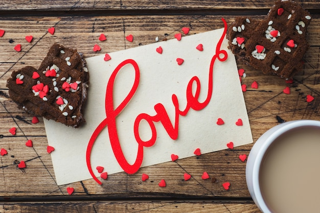 Concept valentine's day. cup of coffee and cookies on a wooden table. greeting card.