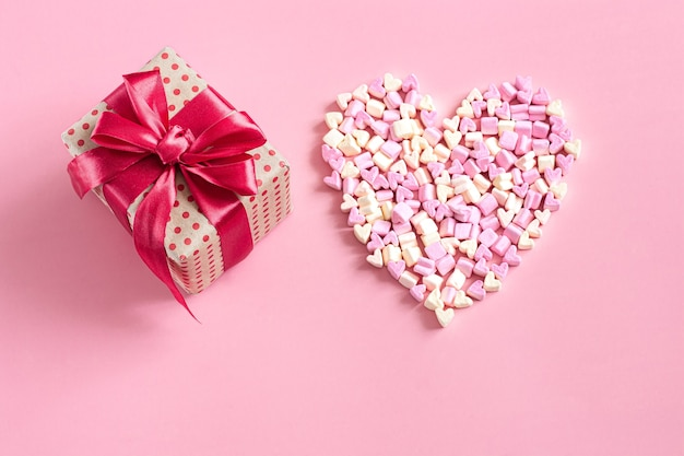 The concept of valentine's day. gift box with red bow on pink wall.
