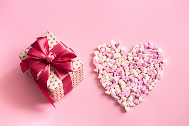 The concept of valentine's day. gift box with red bow on pink.