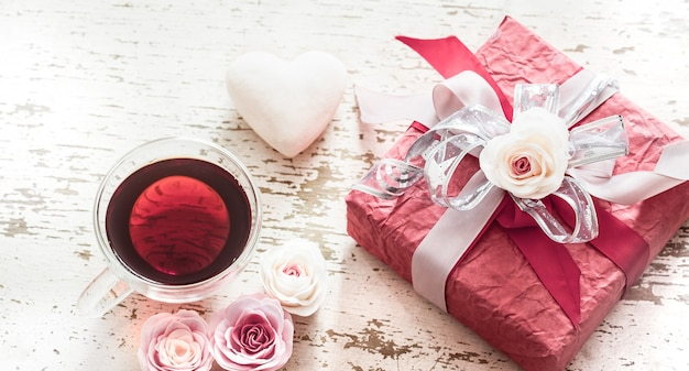 The concept of valentine's day and mother's day, a red gift box with a bow with roses and a cup of tea on a light wooden background