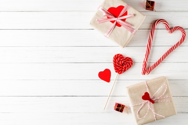 Concept of valentines day. heart shaped candy and gift boxes on white wooden