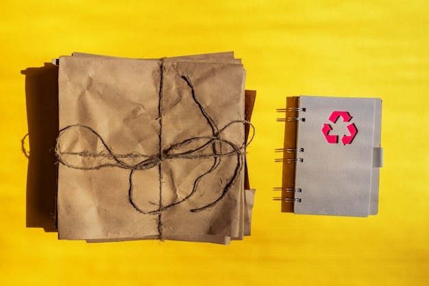 Concept of waste paper recycling process. note book made of reusable wrapping paper with recyclig symbol on a cover on orange background.