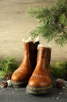 Concept of winter clothes with boots on dark wooden table.
