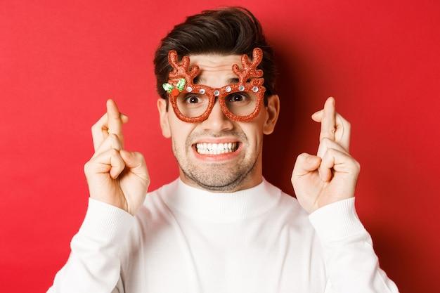 Concetto di vacanze invernali, natale e celebrazione. primo piano dell'uomo speranzoso con gli occhiali da festa, incrociando le dita e esprimendo un desiderio per il nuovo anno, in piedi su sfondo rosso