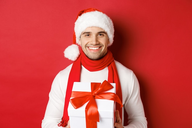 Concept of winter holidays, christmas and lifestyle. close-up of attractive bearded guy in santa hat and scarf, holding a present, giving new year gift and smiling, red background