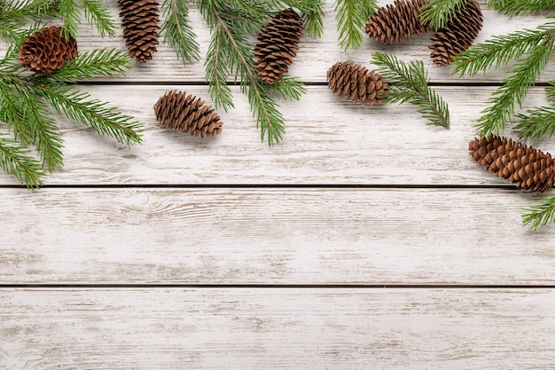 The concept of winter holidays and congratulations. spruce branches and cones on light wooden background, copy space.