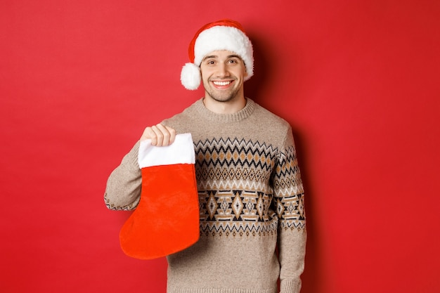 Concept of winter holidays, new year and celebration. image of handsome smiling man in santa hat and sweater, holding christmas stocking for presents and candies, standing over red background