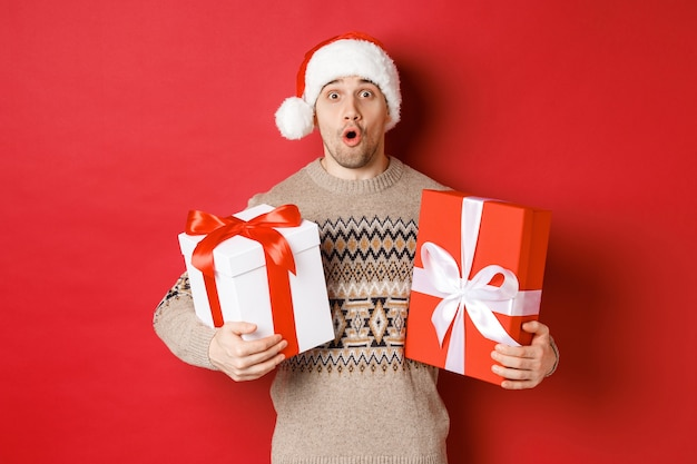 Concept of winter holidays, new year and celebration. image of surprised attractive guy in santa hat and christmas sweater, receiving gifts, holding presents and looking amazed