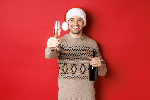 Concept of winter holidays, new year and celebration. portrait of handsome man in santa hat and sweater, holding champagne, raising glass and saying cheers on christmas party