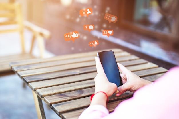 スマートフォンを使用し、ソーシャルネットワーク上でいいね、チャンネル登録者、コメントを使ってコミュニケーションする女の子とのコンセプト。