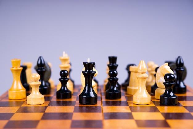 회색 배경에 나무 체스 보드에 체스 조각 개념