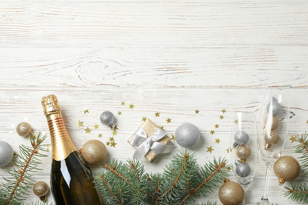 Concept with christmas baubles and champagne on white wooden space, copy space