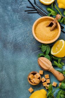 Концепция с ингредиентами для домашнего освежающего лимонада лимонного сока, тростникового сахара и мяты на старом бетонном фоне.