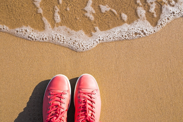 Concept with pink sneakers on bright sea sand. sea summer vacation background with space for the text.