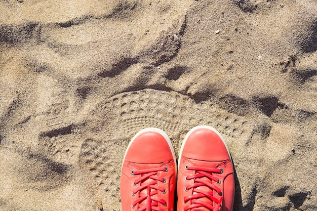 Concept with pink sneakers on bright sea sand. summer vacation background with space for the text.