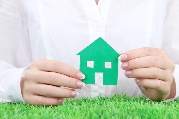 コンセプト:紙の家と女性の手、クローズアップ