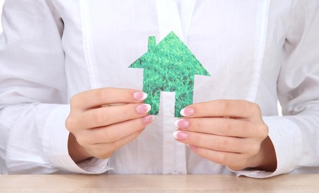 Концепция: руки женщины с бумажным домом