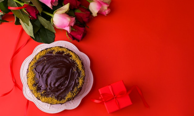 コンセプト女性の日または聖バレンタインの日。新鮮なバラと赤い背景とチョコレートケーキのギフトボックス。上面図。コピースペース