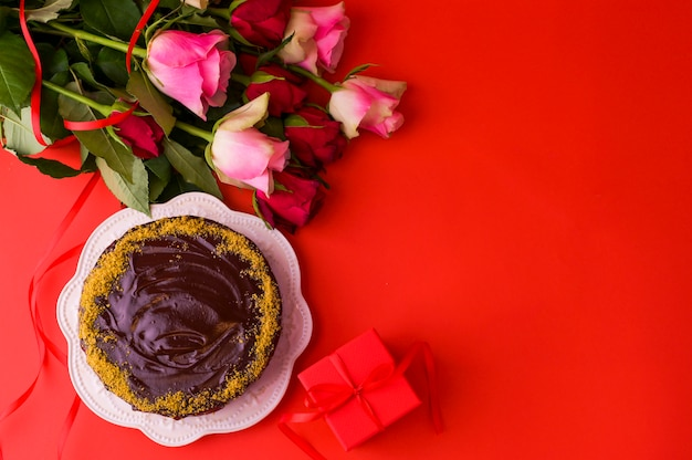 Concept women's day or st. valentines day. fresh roses and gift box on a red background and a chocolate cake . top view. copy space