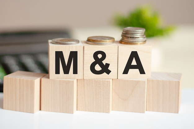 Концептуальное слово m и a на деревянных блоках на красивой поверхности из зеленого цветка