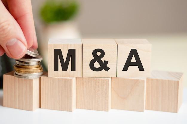Концепция слова m и a на деревянных блоках от зеленого цветка