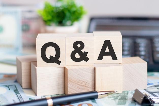 ドル札からの美しい壁の木製ブロックの概念語qとa。コインと電卓ビジネスコンセプトを持つ木製の立方体の単語qとa。