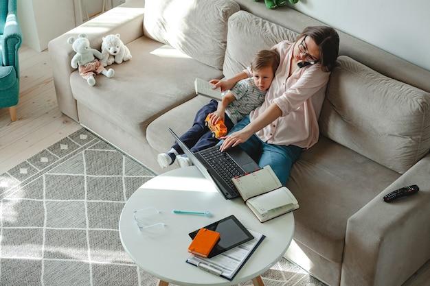 在宅勤務と家庭教育、ラップトップで働く母親