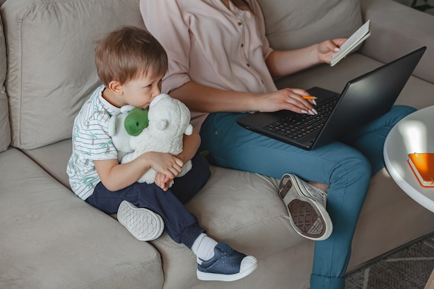 Concept work at home and home family education, mother working with laptop