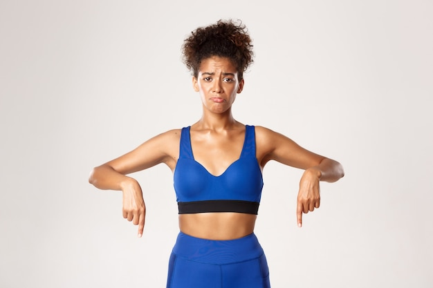 Concept of workout and fitness. sad and gloomy african-american girl athelte, wearing blue