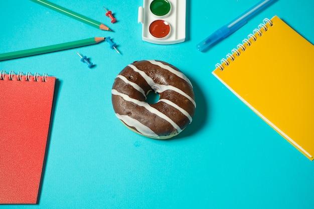 学校でのコンセプト間違った食べ物。脳の充電。学校の文房具の周りの青い背景にチョコレートドーナツ。青色の背景に等尺性モックアップ。クリエイティブフラットは学校に戻る