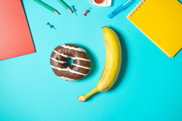 Еда концепции неправильная против здоровой еды в школе. заряд для мозга. шоколадный пончик и банан на синем фоне вокруг школьных канцтоваров. изометрические макет на синем. обратно в школу. легкая закуска