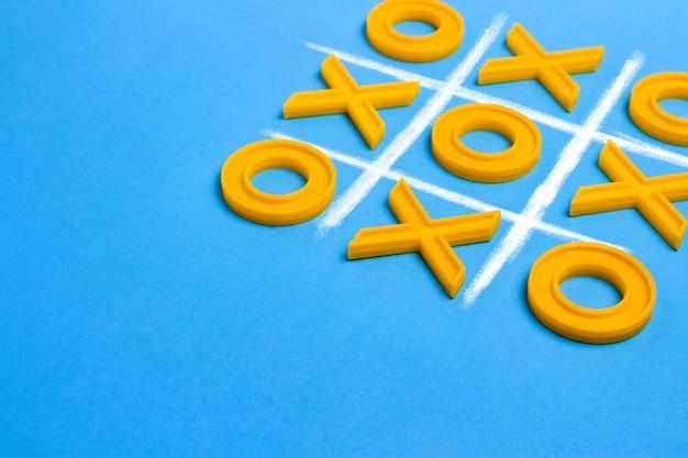 黄色のプラスチック製の十字架とつま先と青の背景に三目並べを再生するための罫線。 concept xo winチャレンジ。子供のための教育ゲーム