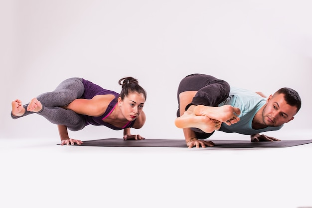 Concept of yoga exercises. young healthy couple in yoga position on white background