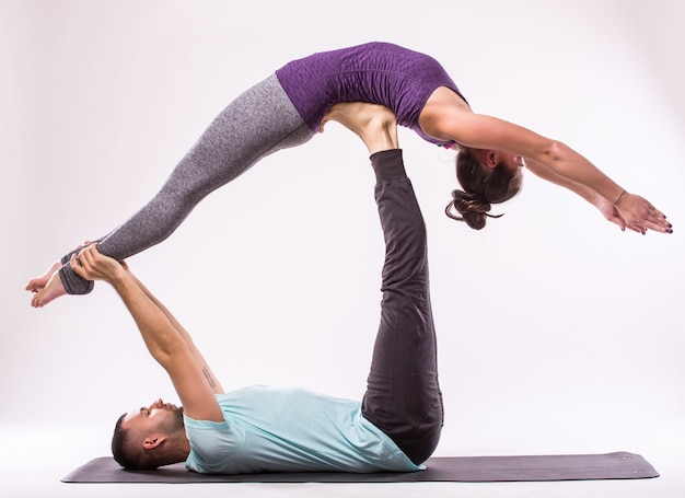 Concetto di esercizi di yoga. giovani coppie in buona salute nella posizione di yoga su priorità bassa bianca