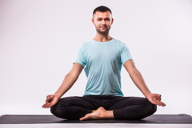Concept of yoga. handsome man doing yoga exercise isolated on a white background