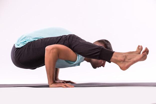 Concetto di yoga. uomo bello che fa esercizio di yoga isolato su sfondo bianco